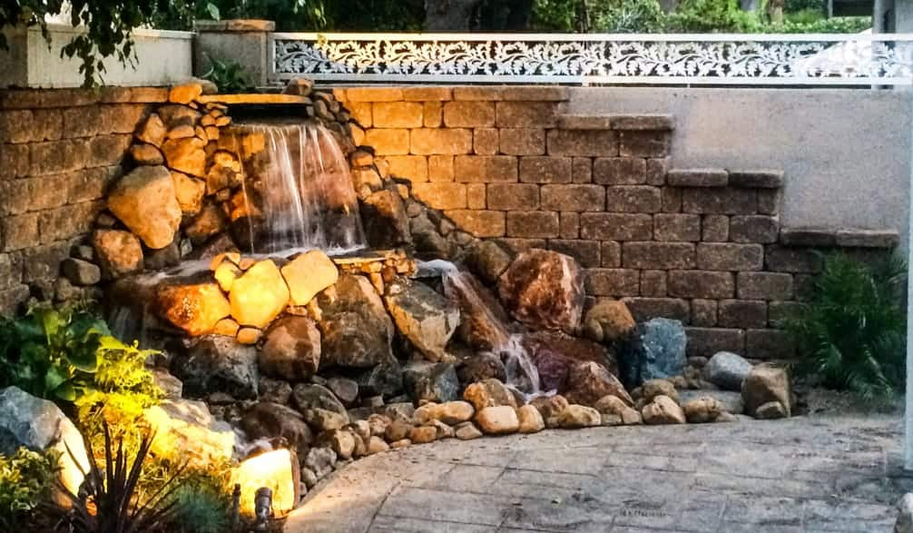 pondless waterfall with water cascading over boulders in residential backyard