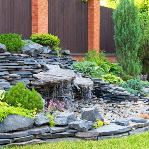 pebble stone waterfall with no water building up - pondless waterfall