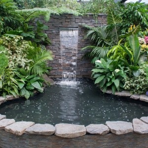 stainless steel wall fountain cascading into a pond